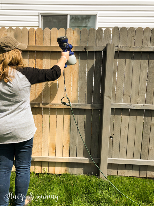 spraying stain on fence