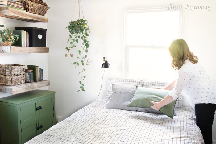 Bedroom with green cabinets and wood shelves